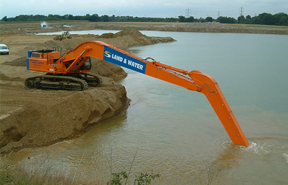 Long-reach excavator performing dredging