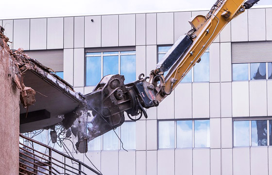 Long-reach excavator performing demolition works